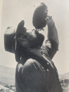 Colin Fletcher drinking water from a canteen while hiking the Grand Canyon.