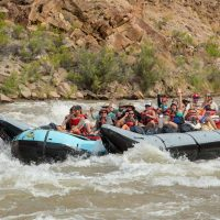 Grand Canyon raft coming through colorado river rapids.